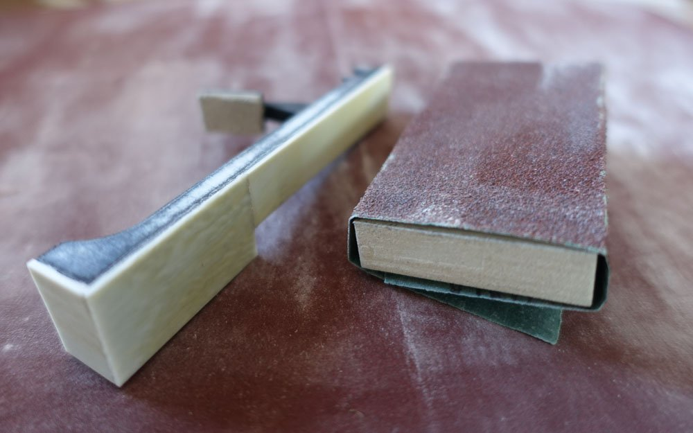 sanding a melodica key with ivory